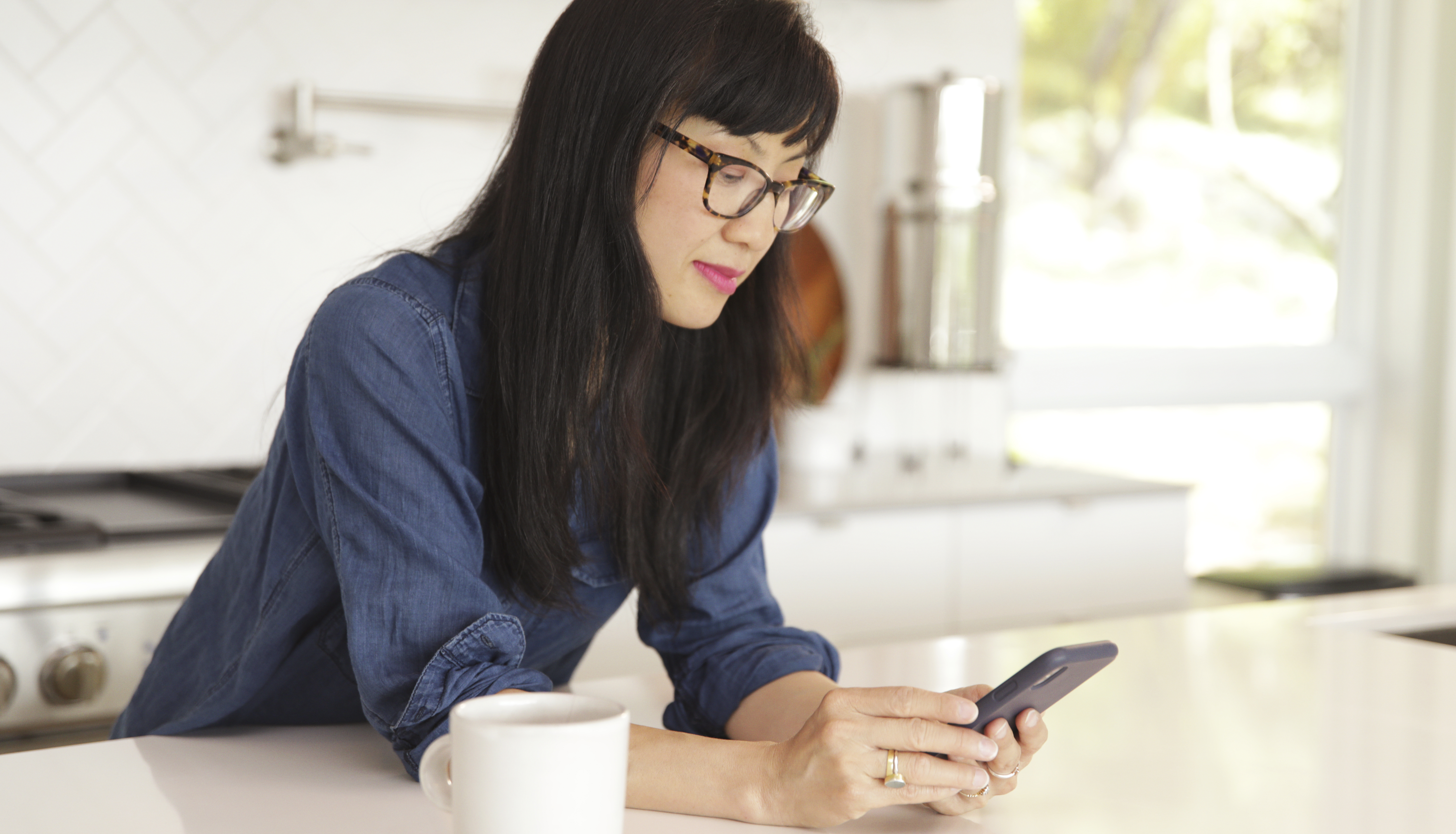 Woman in kitchen looking at phone